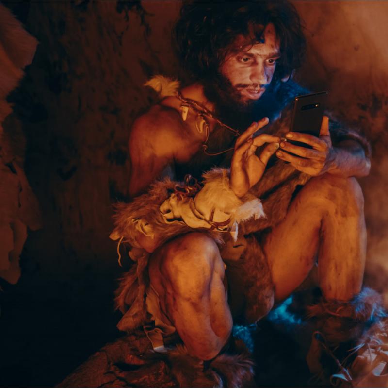 a caveman using a mobile phone