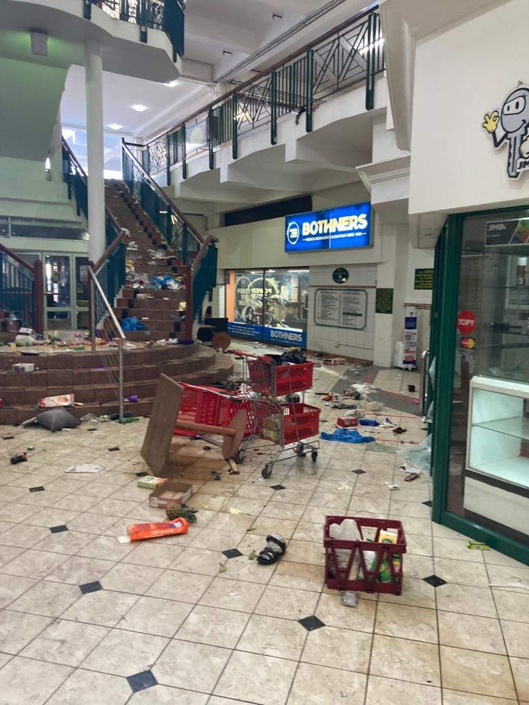 A pillaged shopping mall in South Africa with rubbish strewn across the floor
